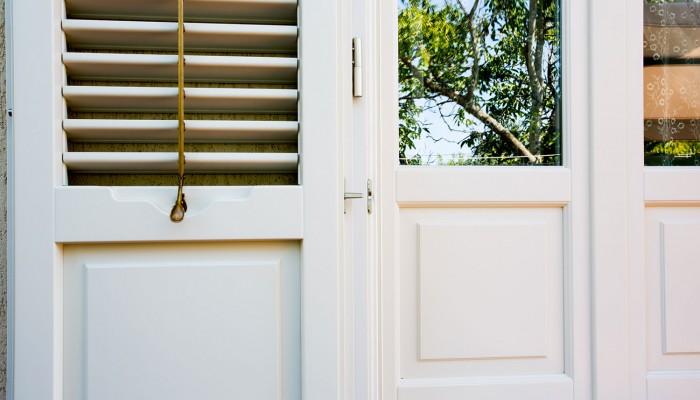 Particolare infisso e persiana in legno laccato bianco.